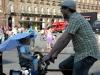 Папа на велосипеде везет дочку в багажнике под зонтиком