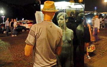 Голая женщина в стеклянной кабине на площади Турина.