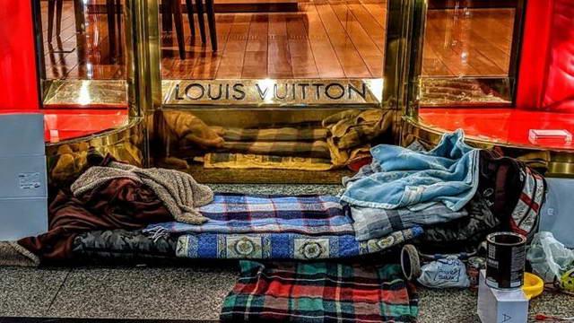 Бездомный спит перед входом в магазин Louis Vuitton на Виа Рома в Турине